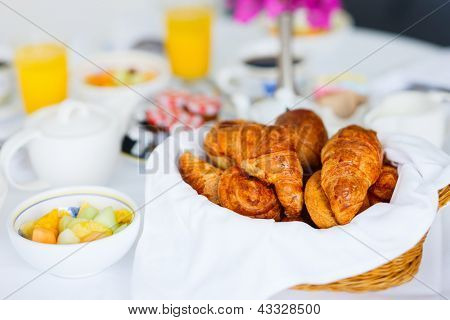 Selection of freshly baked pastry and fruit salad served for breakfast