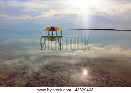 Medical beach on the Dead Sea, Israel. Round gazebo in the water near the water's edge. Cloudy sky reflected in water
