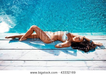 beautiful young woman in bikini lie by the pool summer day