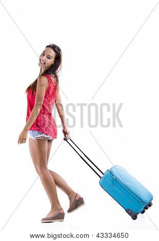Happy woman going on vacation and walking with a suitcase