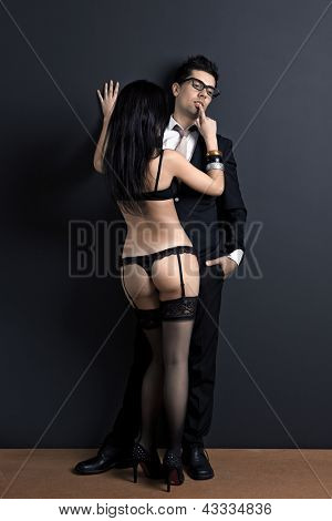 Business man and a sexy young woman in lingerie. Concept about work and pleasure