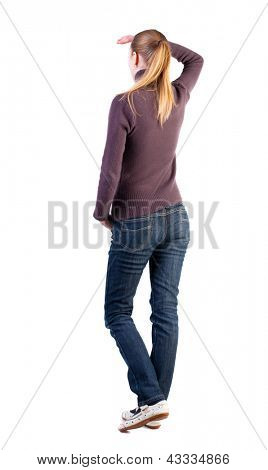 back view of standing young woman. girl hand covers his eyes from bright light. girl in jeans  watching. Rear view people collection. backside view of person.  Isolated over white background