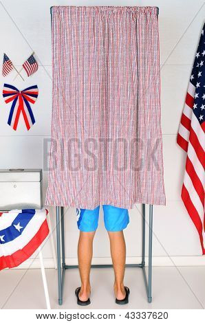 A Young male Voter inside a Voting Booth at his local polling place.