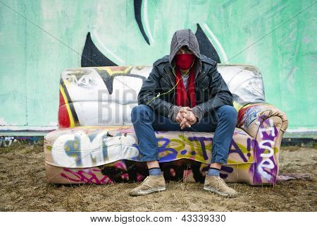 Young man with an attitude sitting with a scarf over his mouth to disguise himself on a graffiti clad couch in front of a concrete, spray painted wall