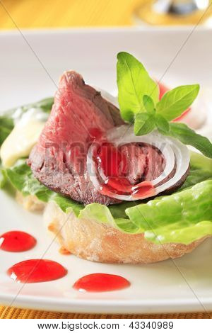 bread with slice of roastbeef and salad, decorated with drops of red sauce