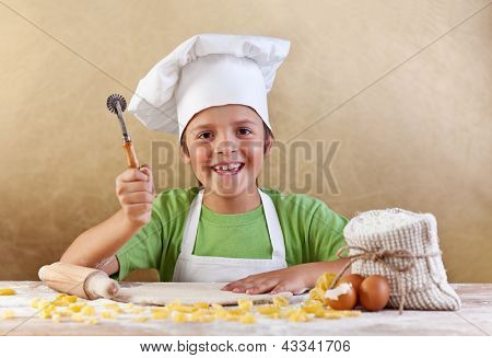 Happy kid with chef hat making pasta or cookie with the dough stretched