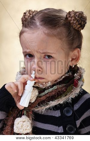 Little girl with the flu using nasal spray reluctantly
