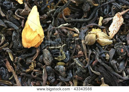 Dry black tea flavored with dry flower buds background