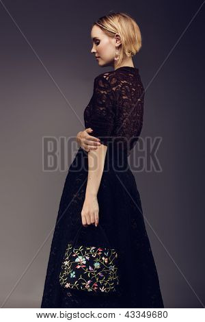 beautiful fashion portrait of a young woman wearing lace top and skirt and an embroidered luxury bag on dark studio background