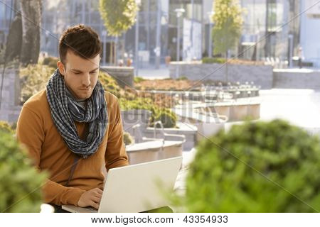 Young man sitting in citypark, using laptop computer.