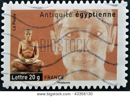 A stamp printed in France dedicated to ancient Egypt shows sculpture of a seated scribe