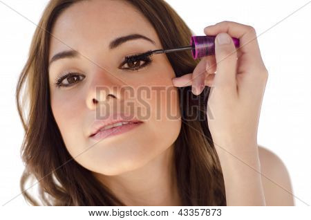 Cute girl putting some mascara on