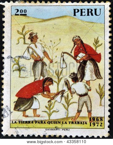 A stamp printed in Peru shows Indians working the land with the message: the land to the tiller