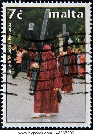 A stamp printed in Malta shows penitents carrying the cross at Easter