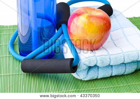Healthy Lifestyle Concept - Bottle Of Water, Apple, Expander And Towel.