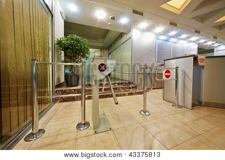 Entrance equipped with tripod-turnstile and sign PRODUCE A PASS