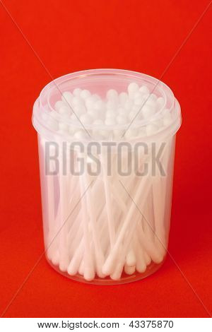 White cotton sticks in plastic container on a red background