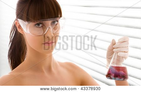closeup of beautiful lab worker holding up test tube