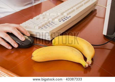 woman working on a computer with some banana to eat