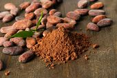 foto of cocoa beans  - Cocoa beans and cocoa powder on wooden background - JPG