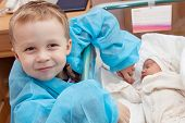 stock photo of bassinet  - Boy rejoices birth of his little sister - JPG