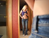 stock photo of stomach  - A young girl is looking at herself in the mirrior and pinching her stomach fat for a diet or self esteem concept - JPG