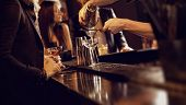 stock photo of vodka  - Bartender using a shaker and pouring wine into the wine glass - JPG