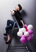 stock photo of adolescent  - Pretty cheerful fashion retro model teen girl laughing on ladder in studio with balloons - JPG