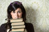stock photo of librarian  - Upset female student holding old books on retro background before exam - JPG