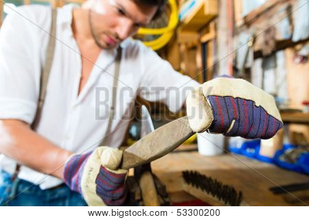 Young man in the Bavarian mountains grinds his axe and sharpening tools with a grindstone to chop the fire wood