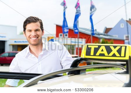Experienced taxi driver in front of his taxi, waiting for a passenger