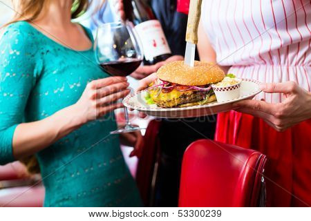 Friends or couple eating fast food in American fast food diner, the waitress serving the food, burgers, fries, and red wine