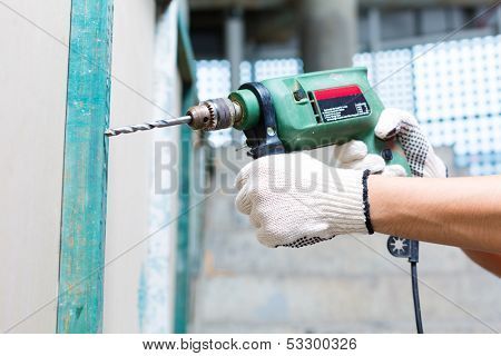 Asian Indonesian builder or craftsman drilling with a machine or drill, protection gloves and tools in a wall of a tower building or construction site