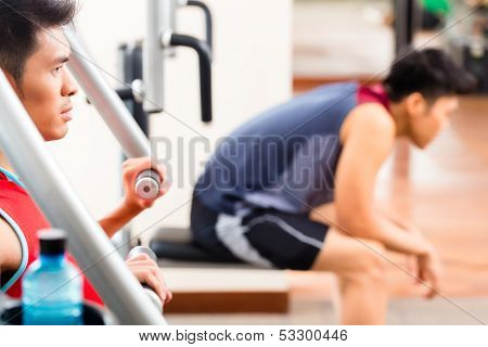 Chinese men having fitness training or workout in gym doing sport to build up muscle on a weight machine