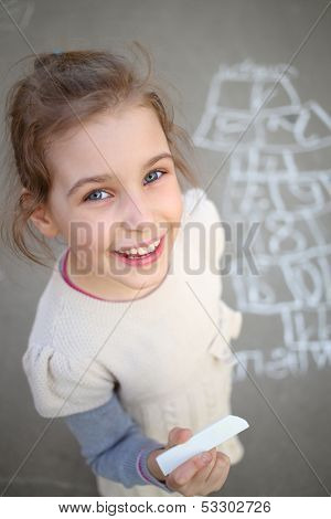 A smiling girl with white chalk in hand standing next to a hopscotch
