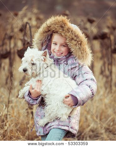 happy girl with her dog  in a field in autumn