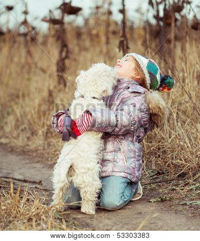 little cute girl with her dog breed White Terrier walking in a field