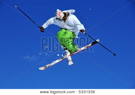 Skier In Green And White Performing A Jump
