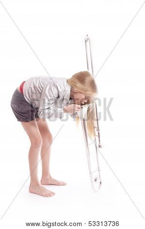 Young Girl In Silver Jacket Looking Into Her Trombone