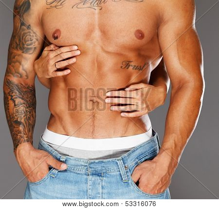Woman's hands embracing man with naked muscular torso