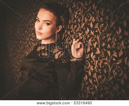 Beautiful young girl wearing black evening dress in luxury interior