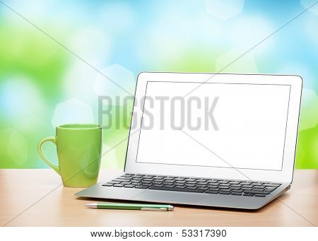 Laptop with blank screen and cup on table over sunny day bokeh background