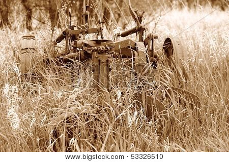 Antique Plow Overgrown in a Field in Sepia