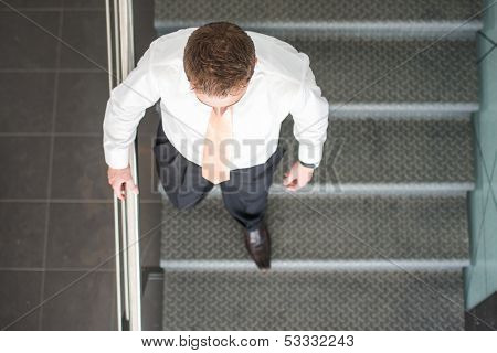 Sleek corporate man ascending stairs