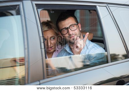 Two corporate looking modern people sitting in a car backseat