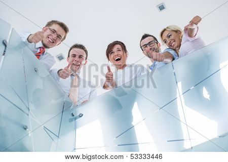 Happy corporate people posing showing thumbs up in a modern office