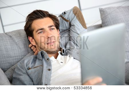 Attractive man at home using digital tablet