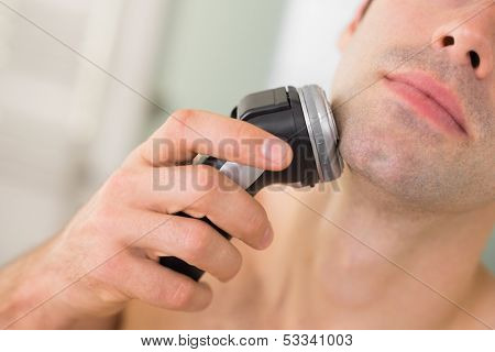 Extreme Close up of a handsome young man shaving with electric razor
