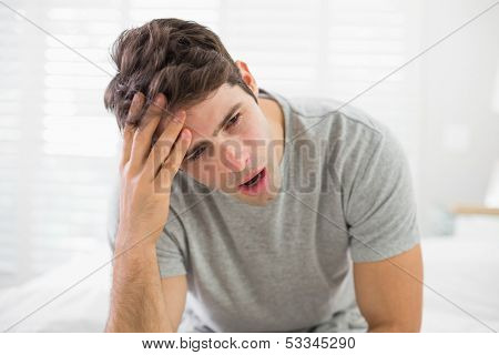 Sleepy young man sitting and yawning in bed at home