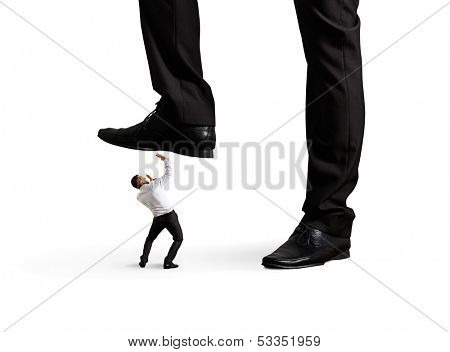 scared small businessman under big leg his boss. isolated on white background